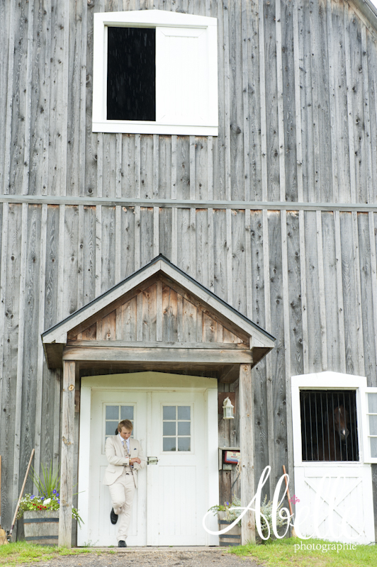 Outdoor groom portrait in front of barn